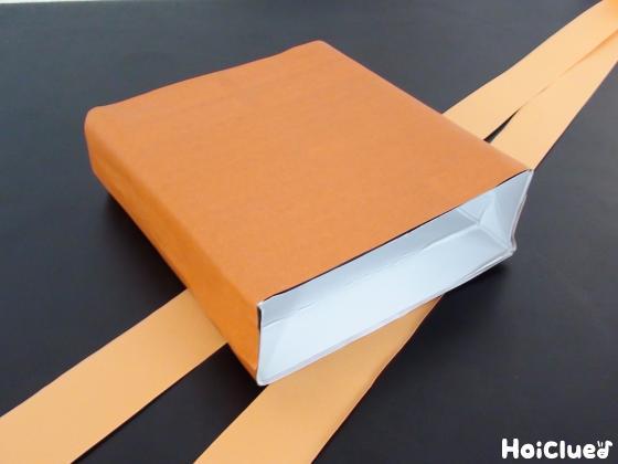空き箱を茶色い折り紙でくるみ細長く切った画用紙を2本作った写真