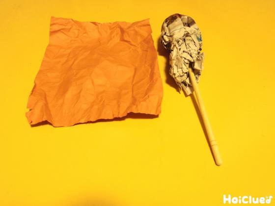 くしゃくしゃにして開いた色画用紙と、割り箸に新聞紙を巻き付けた写真
