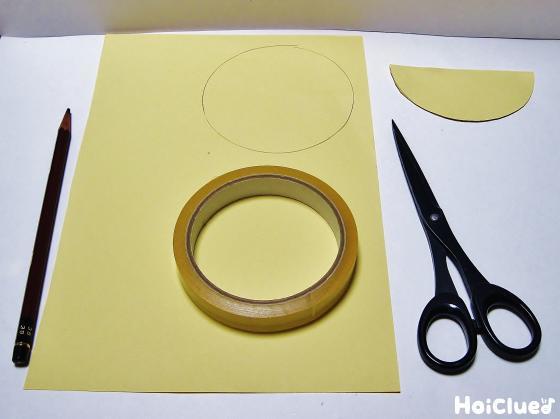 色画用紙を円形に切り半分に折る様子