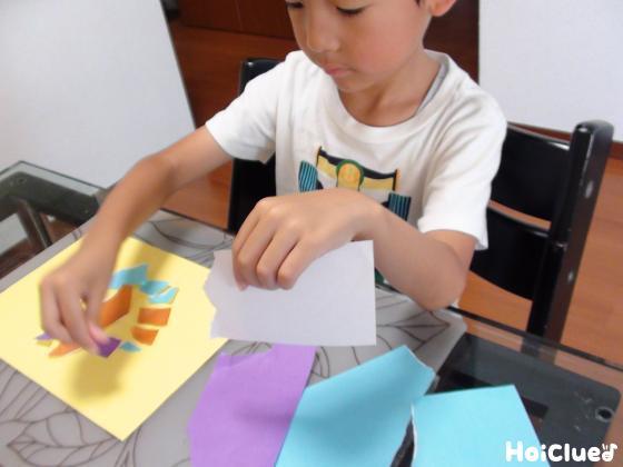 長方形の色画用紙の上にちぎった画用紙を貼る子どもの様子