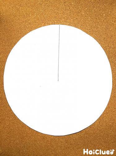 円形に切った画用紙に切り込みを入れる様子