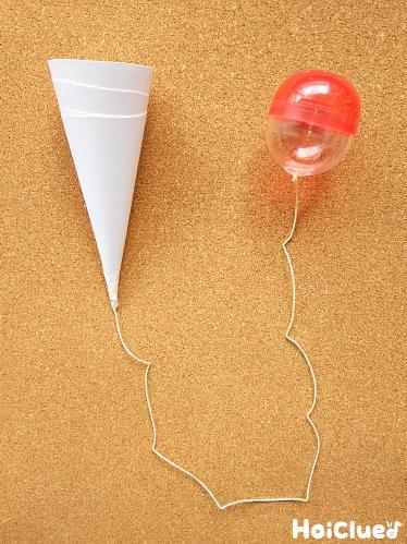 丸めて円錐形を作り、ガチャガチャの容器とタコ糸で固定した写真