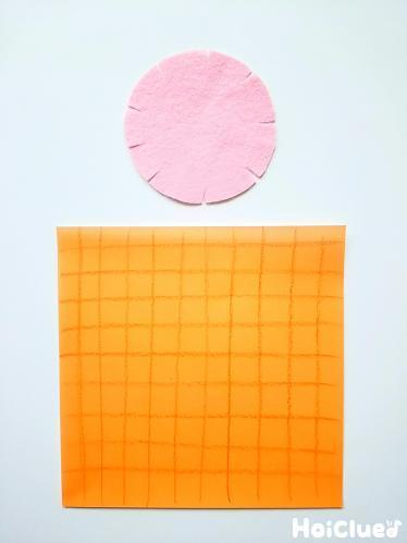 丸く切ったフェルトと格子模様を描いた折り紙の写真