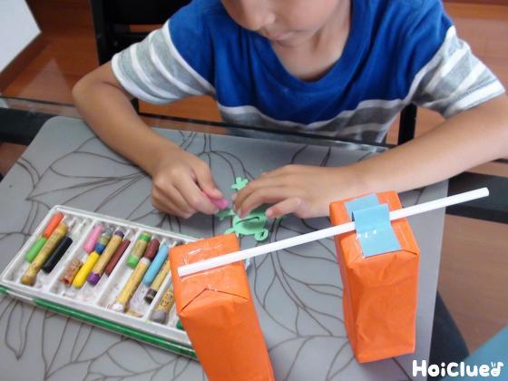 画用紙で作ったカエルに絵を描く子どもの様子