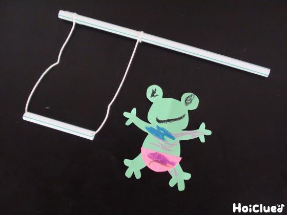 短かく切ったストローにタコ糸を通し、糸の両端を長いストローに結びブランコを作る様子