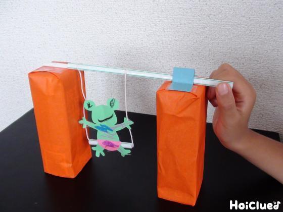 2個の牛乳パックの上に固定した細いストローに、カエルを付けたストローを通した写真