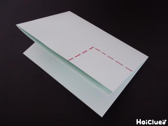 画用紙を折って切っている写真