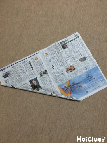 3枚重ねた新聞紙を斜めにくるくると巻く様子