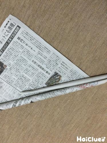 更に新聞紙を巻き長い棒を作る様子