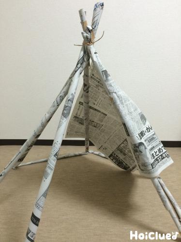 棒で作った骨組を新聞紙で覆っていく様子