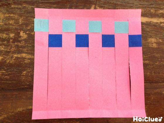 細く切った折り紙を交互に編んでいる写真