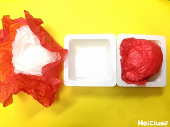 花紙を丸めて容器に入れている写真