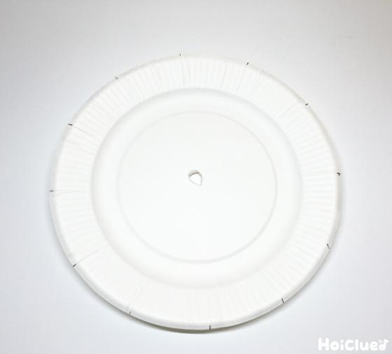 紙皿の真ん中に穴を開けている写真