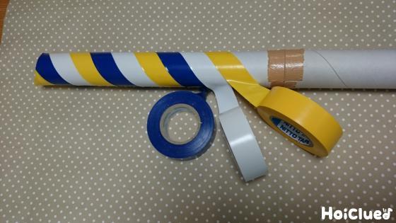 サランラップの芯に3色のビニールテープを交互に斜めに巻いていく様子