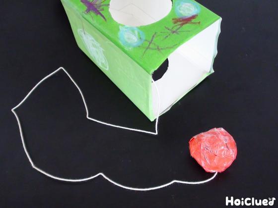 丸めた紙に紐をつけて牛乳パックに取り付けた写真