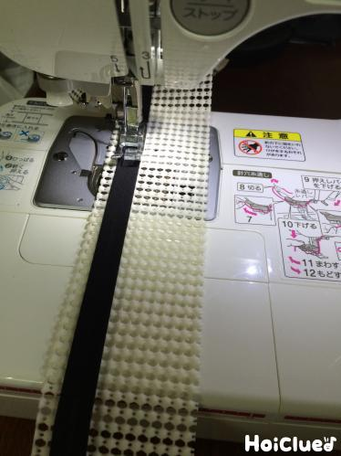 ミシンでシートにバイアステープを縫い付ける様子