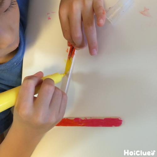 アイスの棒に模様を描く子どもの様子
