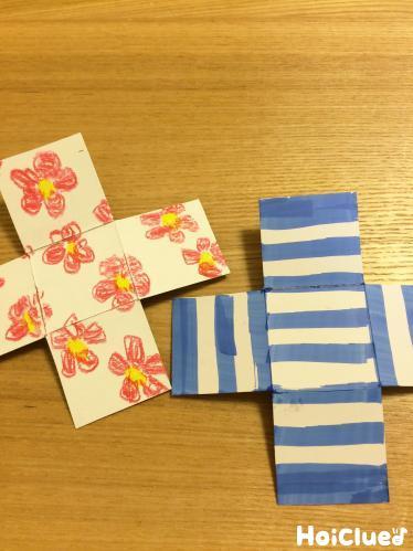 十字形にした2枚の厚紙に模様を描いた写真