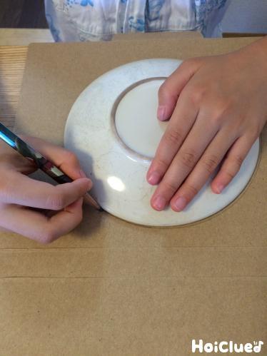 段ボールにお皿を置いて円を描いた写真