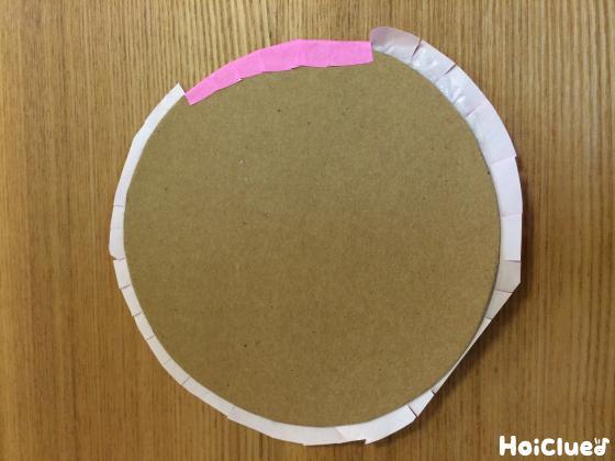 丸く切り抜いた段ボールを折り紙で包んでいる写真