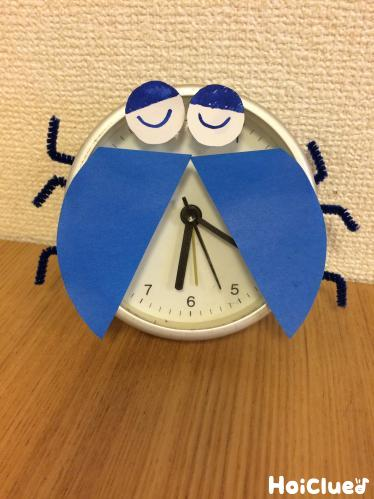 時計に画用紙の羽と目、モールの足を付けてんとう虫の様にした写真
