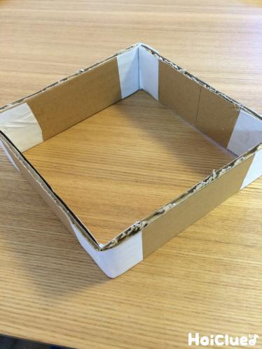 4本のダンボールを四角く繋ぎ合わせコピー用紙で角を留めた様子