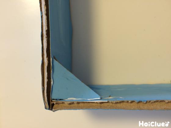フレームの内側の四隅に小さな三角形に切ったダンボールを固定した写真