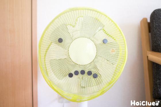 網をかけた扇風機に磁石を顔のように貼り付けている写真