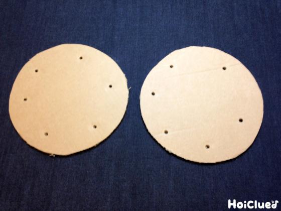 丸く切った2枚のダンボールのフチに沿って何個か穴を開けた写真