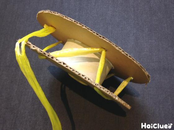 ガムテープの芯を挟んだ2枚のダンボールの穴にスズランテープを通す様子
