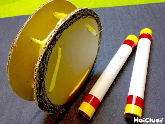 フチを黒く塗ったエイサー太鼓と、ラップの芯2本で作ったバチの写真