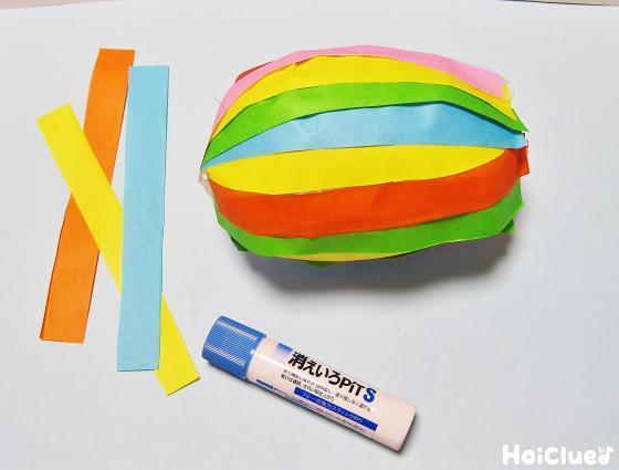 折り紙を細く切って風船に貼り付けている写真