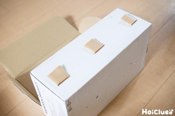 1つの箱の側面にガムテープをつけた写真