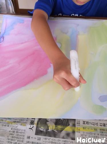 絵の具の上からろうそくで絵を描いている写真