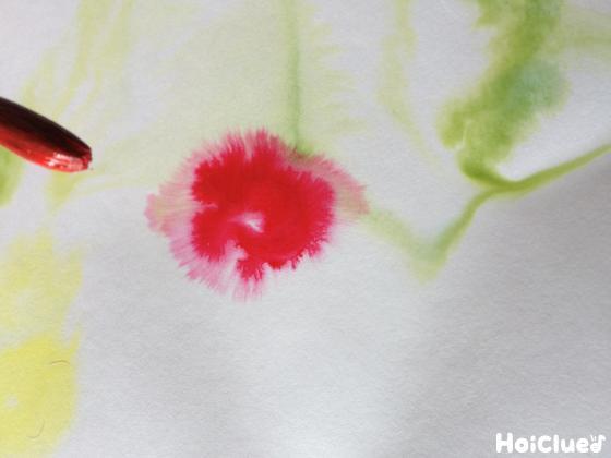 濡らした画用紙に筆で色水を垂らす様子