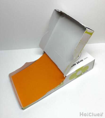 ティッシュ箱に折り紙を挟んでいる写真