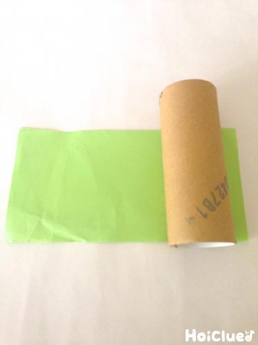 トイレットペーパーの芯の長さに切るために折り紙を巻いている写真