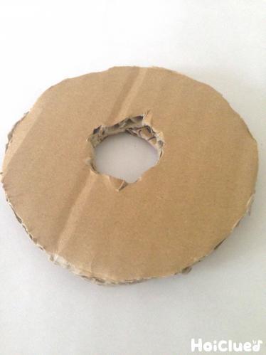 ダンボールをドーナツ型に切り剣のつばを作った写真
