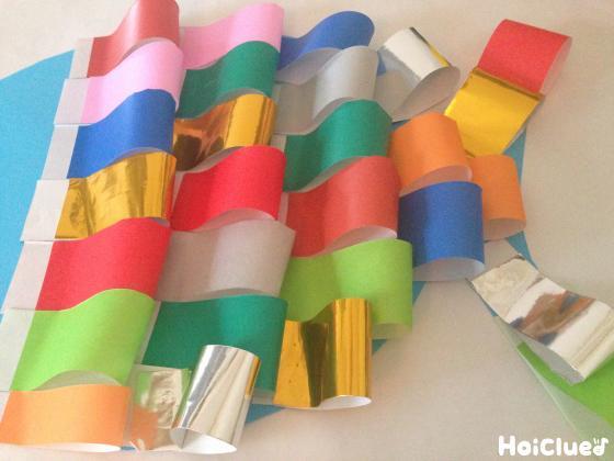 折り紙のうろこをまんべんなく貼り付け完成した魚の写真
