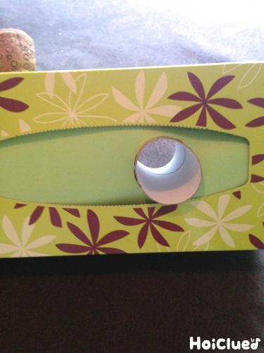 ティッシュ箱の取出口に貼った画用紙にも穴を開けトイレットペーパーの芯を通す様子