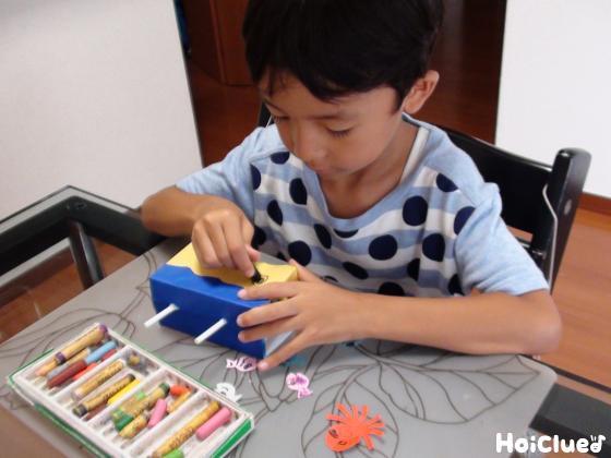 箱の表面に色画用紙を貼り絵を描く子どもの様子