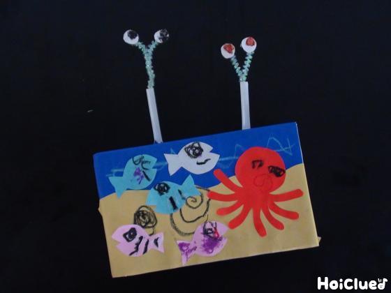 箱に海の生き物を貼り付け、ストローにちんあなごを差し込んだ写真