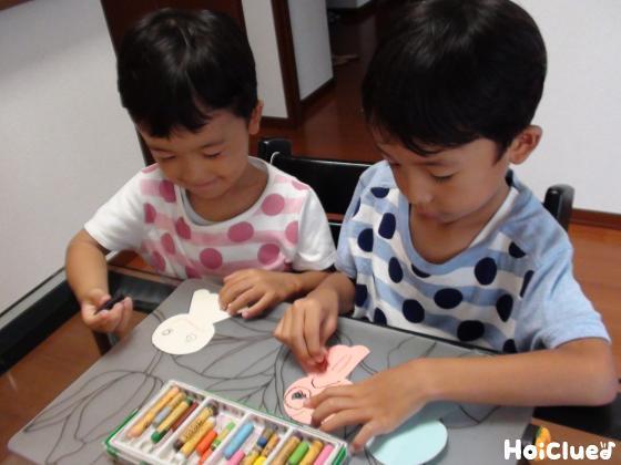 てるてる坊主に絵を描く子どもたちの様子