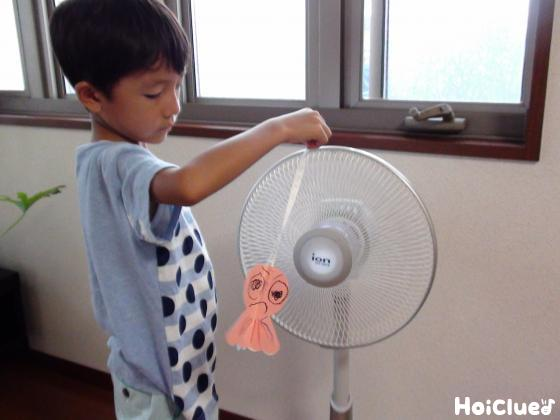 手に持ったてるてる坊主を扇風機にかざす子どもの様子