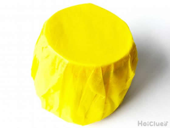 プリンカップを黄色い花紙で覆った様子