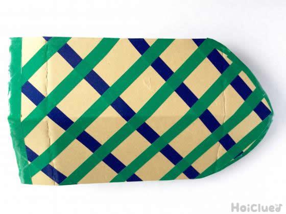 甲羅の形に切ったダンボールにビニールテープで模様をつけた写真