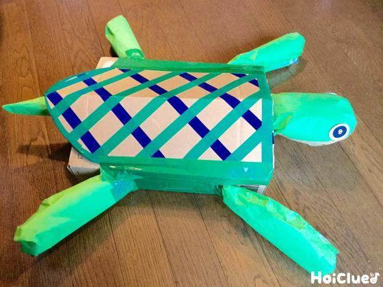 新聞紙を詰めた箱に亀のパーツを取り付け完成した亀の写真