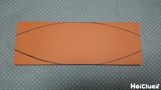 オレンジ色の色画用紙を船形に線を引いてカットした写真