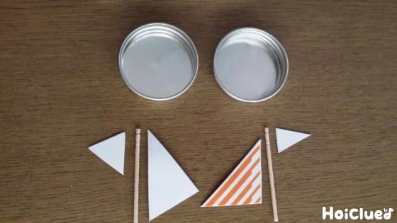 瓶の蓋と先を切った爪楊枝と三角形に切った厚紙の写真
