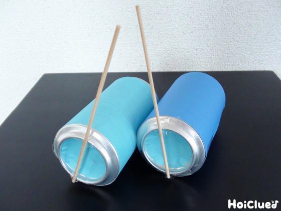 空き缶に水色や青の色画用紙を貼り、底部分にたけひごを取り付けた写真